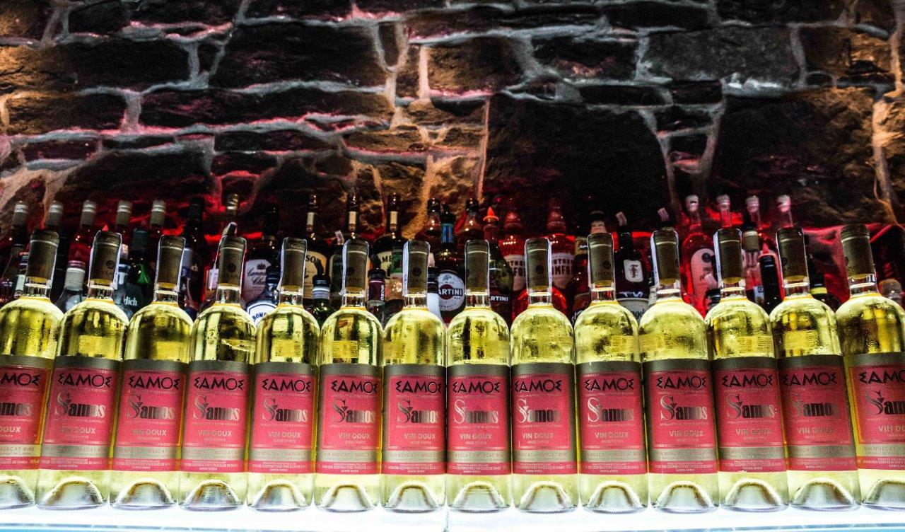A row of samos wine bottles on a table