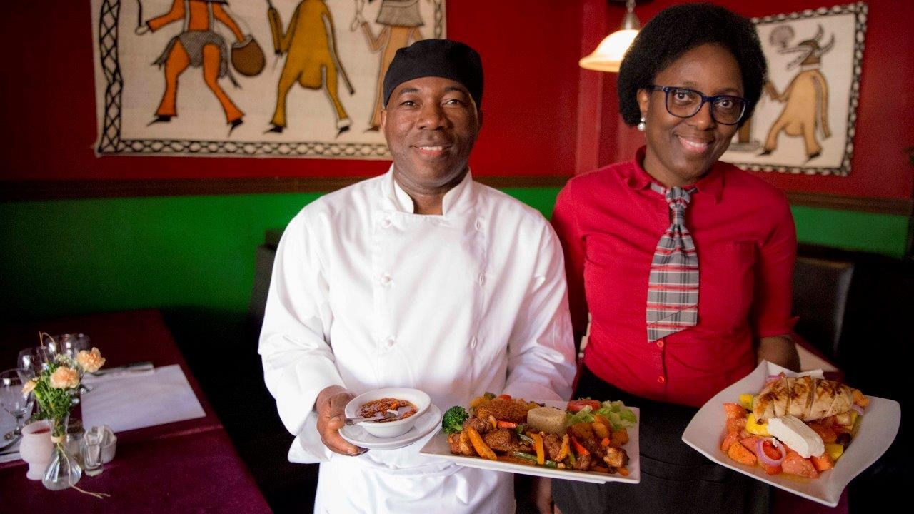 two Akwaba restaurant owner with a plate of food