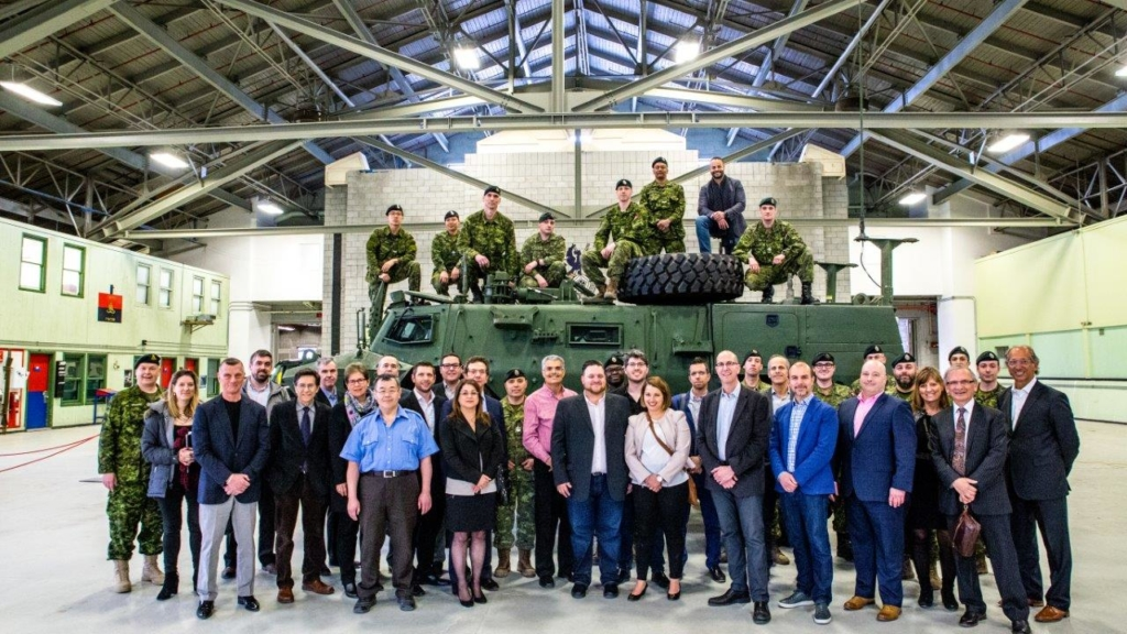 A group of people standing in front of a Canadian army tank