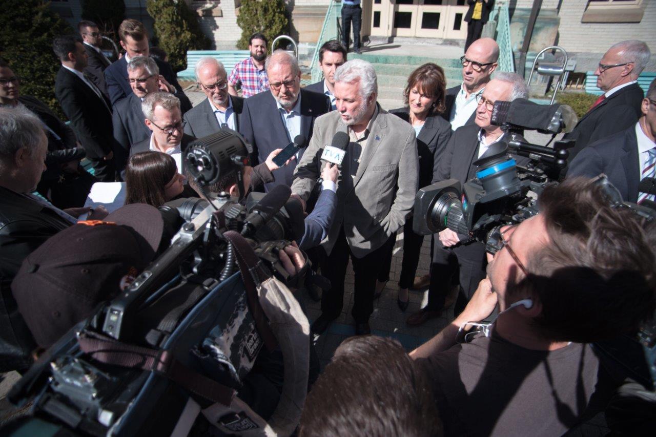 Philippe Couillard Quebec Premier in front of journalist