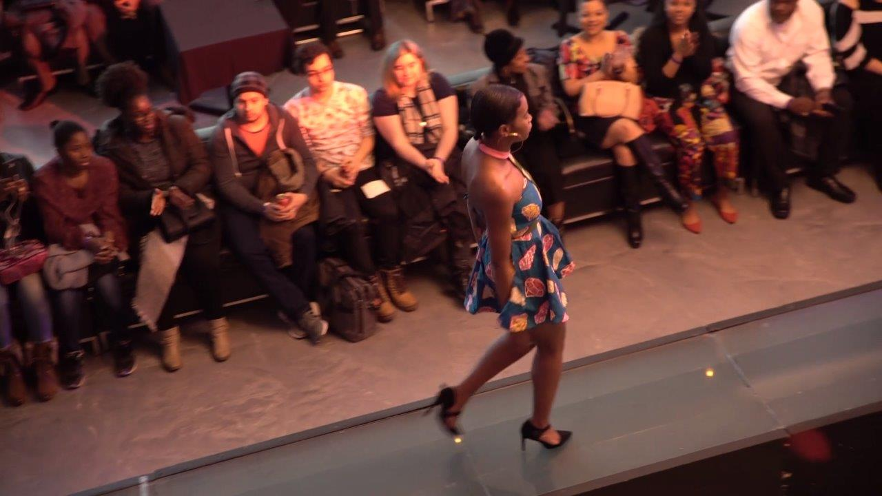 A group of people watching a women on catwalk
