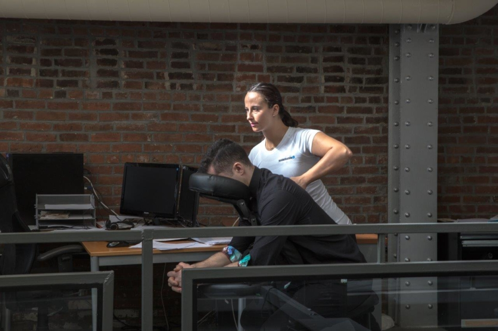 A man in a massage chair by a women in front of a laptop desk