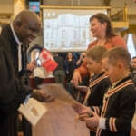 Black men giving certificat to young west european children