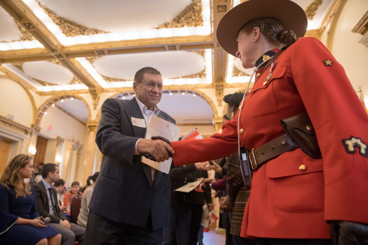 Royal Canadian Mounted Police congratulating men for Canadian citizenship